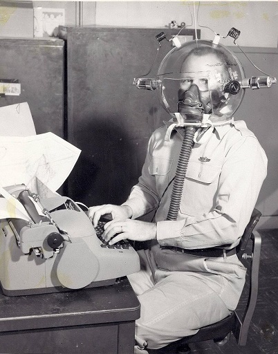 some kind of weird helmet that provides oxygen to an office worker